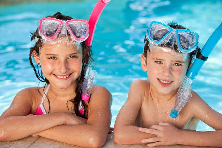 Two kids in a swimming pool with googles and snorkels